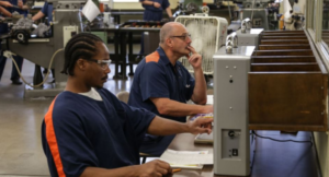 Photo of men who are incarcerated working at a computer